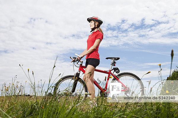 Junge Frau beim Wandern mit dem Mountainbike