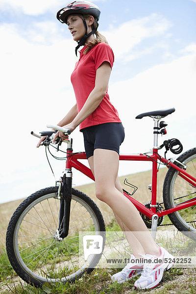 Junge Frau stehend mit Mountainbike