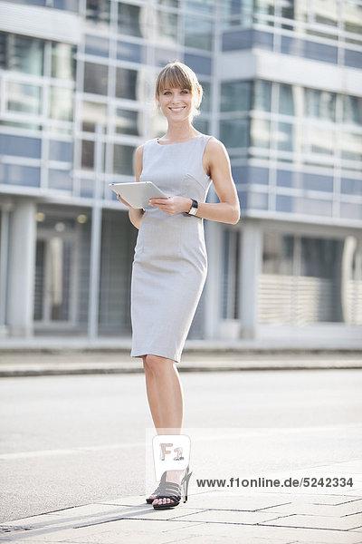 Junge Geschäftsfrau mit digitalem Tablett auf dem Bürgersteig