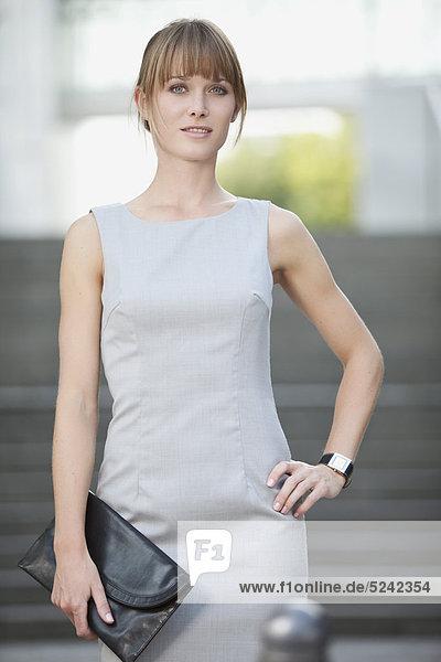 Junge Geschäftsfrau mit Geldbörse  lächelnd  Portrait