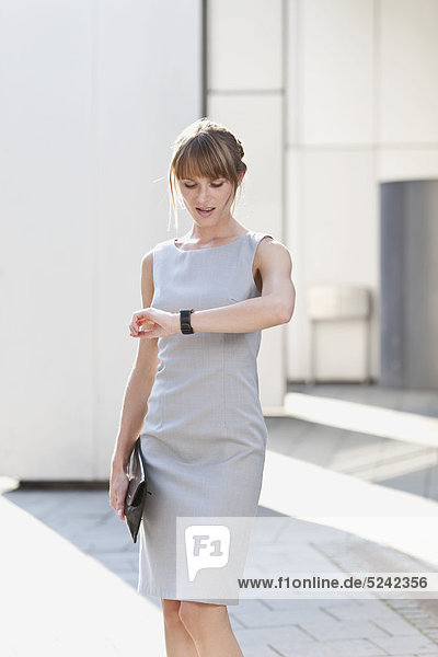 Young businesswoman holding purse and checking time