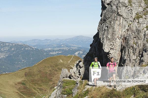 Österreich  Kleinwalsertal  Mann und Frau beim Wandern an Felsen am Berg