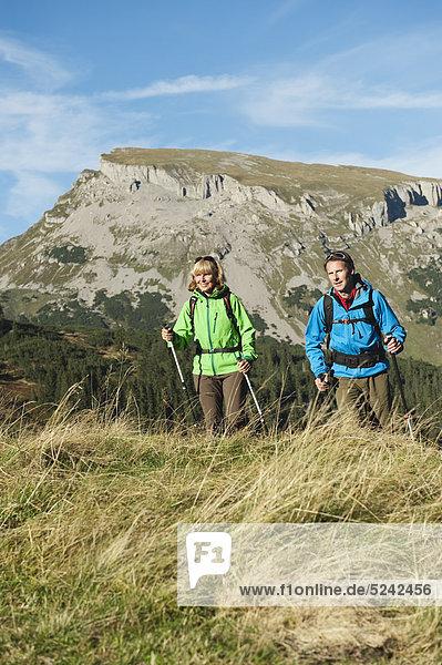 Österreich  Kleinwalsertal  Mann und Frau wandern auf dem Bergweg  lächelnd