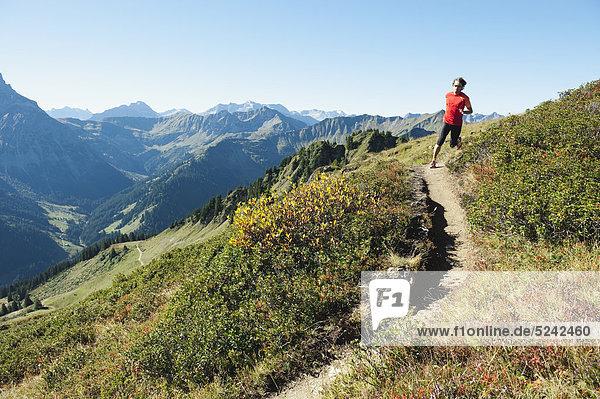 Austria  Kleinwalsertal  Mid adult man running on mountain trail