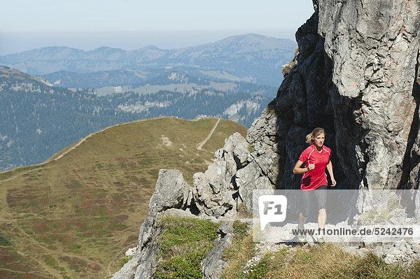 Österreich  Kleinwalsertal  Junge Frau beim Laufen auf dem Bergweg in der Nähe von Felsen