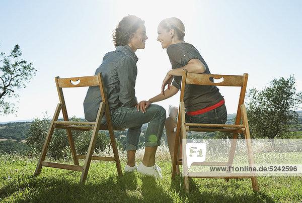 Italien  Toskana  Junges Paar auf Holzstühlen zusammensitzend