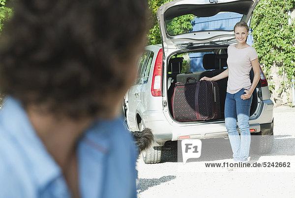 Italien  Toskana  Nahaufnahme von jungem Mann und Auto mit Gepäck im Hintergrund