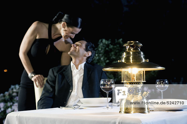 Germany  Bavaria  Couple romancing while candlelight dinner