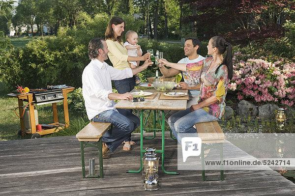 Deutschland  Bayern  Freunde beim Essen und Trinken mit Barbecue im Vordergrund