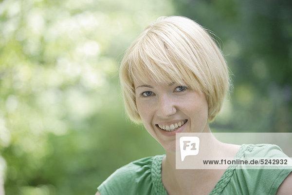 Nahaufnahme einer jungen Frau im Park,  Portrait,  Lächeln