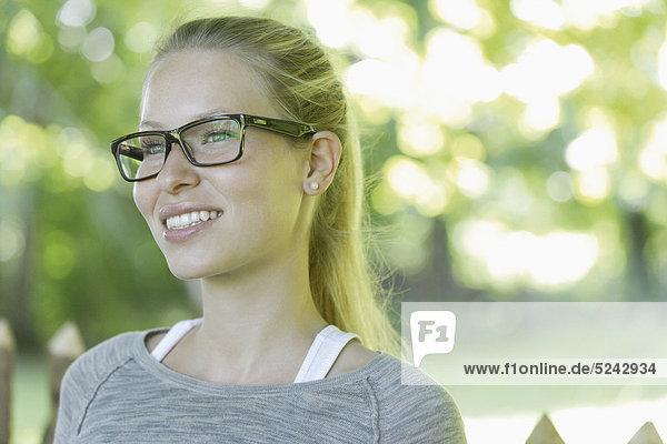 Nahaufnahme einer jungen Frau mit einer dicken Brille  lächelnd