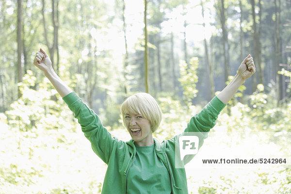 Junge Frau im Wald mit erhobenen Armen  Portrait  lächelnd