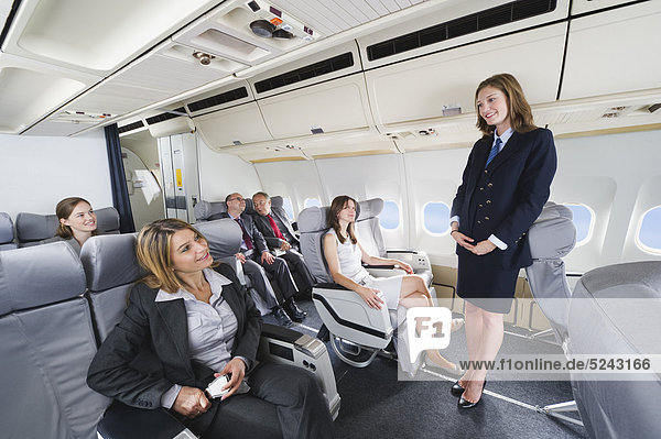 Germany  Bavaria  Munich  Stewardess and passengers in business class airplane cabin  smiling