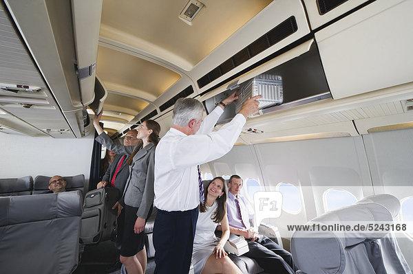Deutschland  Bayern  München  Fluggäste  die Handgepäck aus dem Regal in der Business Class Flugzeugkabine nehmen.