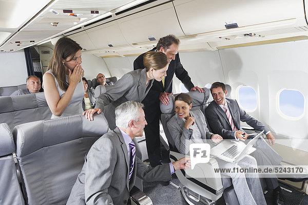 Deutschland  Bayern  München  Gruppe von Passagieren  die im Laptop in der Business Class Flugzeugkabine suchen  lächelnd