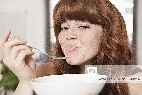 Nahaufnahme einer jungen Frau beim Müsliessen  lächelnd  Porträt