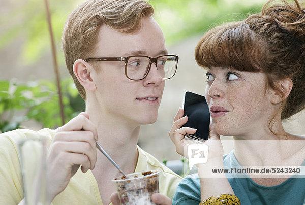 Deutschland  Berlin  Nahaufnahme des jungen Paares beim Telefonieren und Flüstern