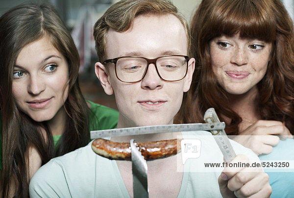Close up of young man measuring grilled sausage and women beside him  smiling