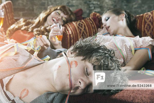 Nahaufnahme von jungen Männern und Frauen  die sich nach der Party auf der Couch entspannen.