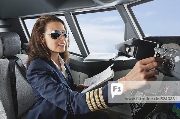 Frau Flugkapitän mit Karte im Flugzeugcockpit WESTF017032