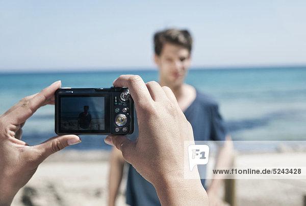 Spanien  Mallorca  Junge Frau fotografiert Mann am Strand