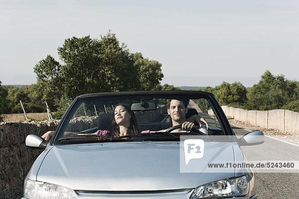 Spanien  Mallorca  Junges Paar im Cabriolet unterwegs