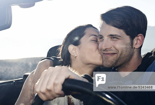 Spain  Majorca  Young woman kissing man in cabriolet car  close up
