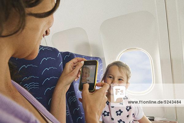Frau und Mädchen mit Handy im Economy Class Airliner