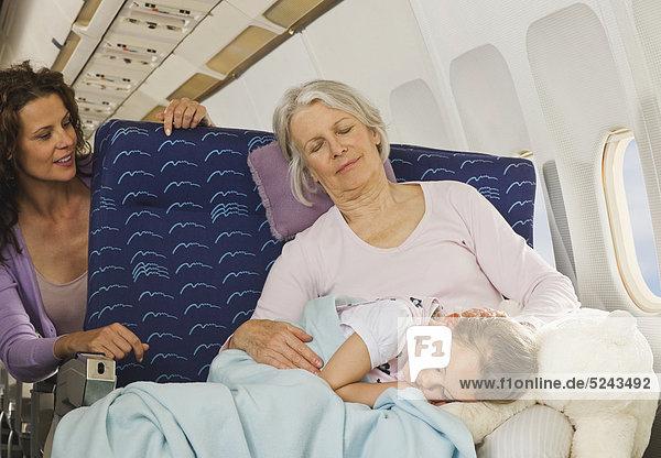 Seniorin und Seniorin schlafen neben dem Fenster im Economy Class-Flugzeug