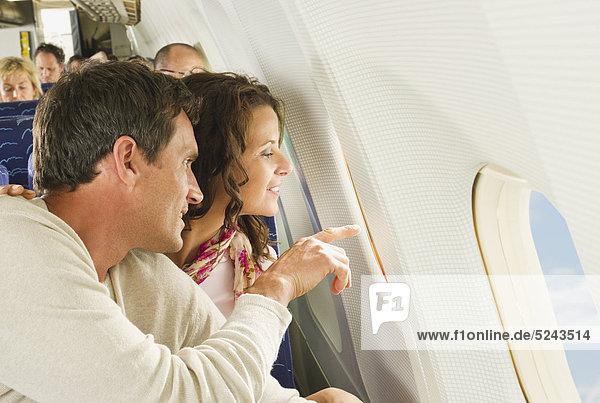 Mann und Frau blicken aus dem Fenster in einem Economy Class Flugzeug