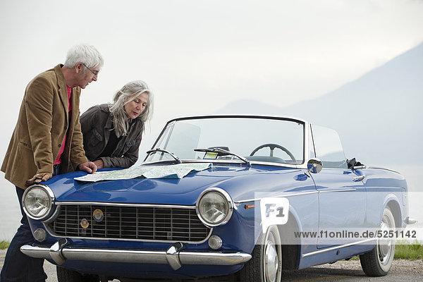 Seniorenpaar mit Straßenkarte an einem Cabrio  Italien  Gardasee