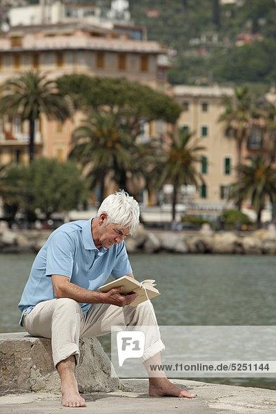 Senior sitzt mit Buch am Wasser  Italien  Rapallo Senior sitzt mit Buch am Wasser, Italien, Rapallo