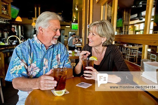 A happy middle aged married couple enjoy iced tea together in a Long Beach  CA  restaurant