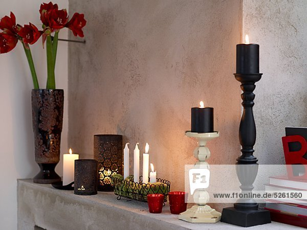 Verschiedene Kerzen und Vase am Kamin