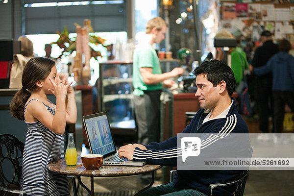 Vater und Tochter mit Laptop im Café