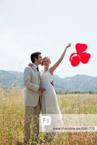 Frischvermählte im Feld mit roten Herzballons Frischvermählte im Feld mit roten Herzballons