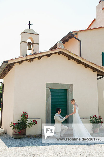 Jungvermählten außerhalb der Kirche  Bräutigam auf ein Knie Jungvermählten außerhalb der Kirche, Bräutigam auf ein Knie