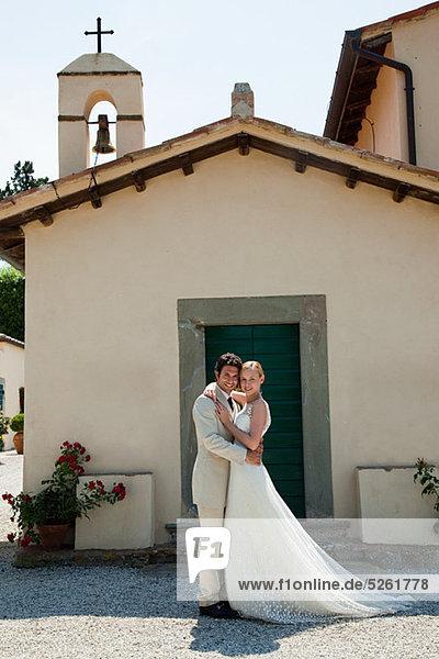 Jungvermählten außerhalb der Kirche  umarmen Jungvermählten außerhalb der Kirche, umarmen