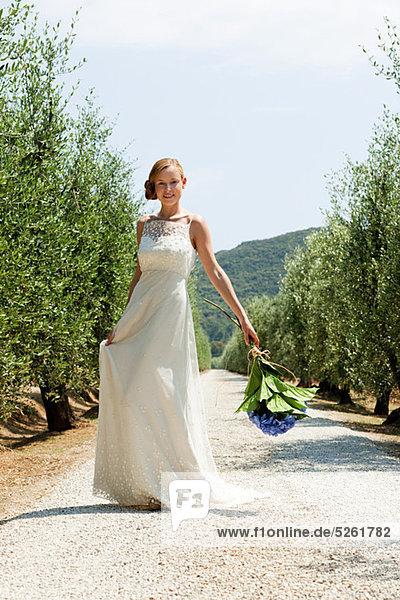 Braut auf der Landstraße mit Blumenstrauß Braut auf der Landstraße mit Blumenstrauß