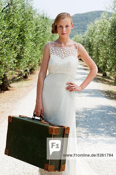 Braut mit Koffer auf der Landstraße  Hand auf Hüfte Braut mit Koffer auf der Landstraße, Hand auf Hüfte
