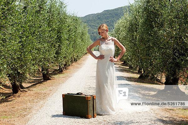 Braut mit Koffer auf Landstraße  die Hände auf den Hüften