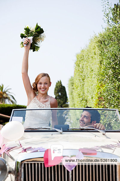 Newlyweds in classic car  bride holding bouquet
