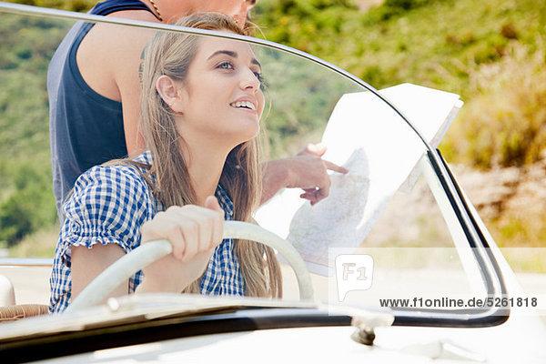 Junge Menschen mit convertible Car Blick auf Karte