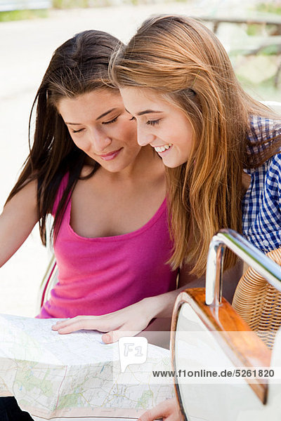 Junge Frauen mit convertible Car Blick auf Karte
