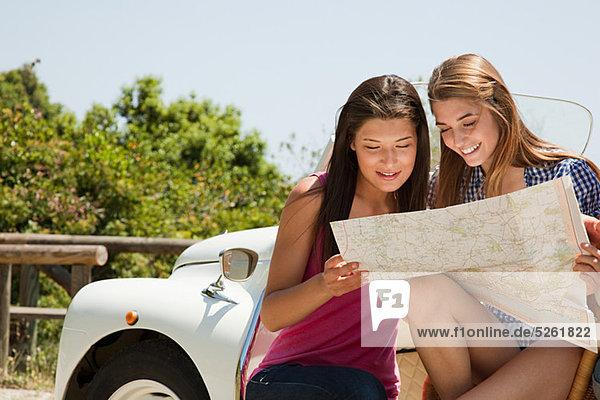 Junge Frauen mit Cabriolet auf der Landkarte