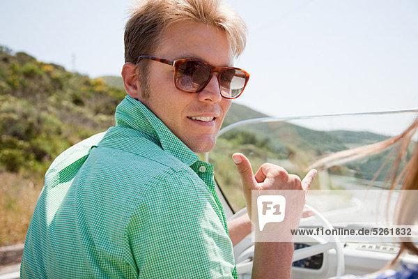 Junger Mann mit Sonnenbrille beim Cabriofahren