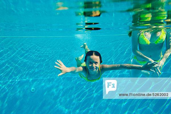Frau mit Mädchen im Schwimmbad  Unterwasseransicht