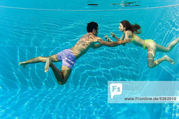Junges Paar schwimmt im Schwimmbad  Unterwasserblick