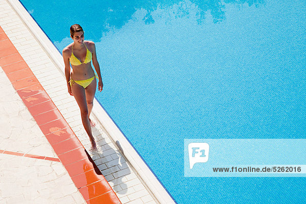 Junge Frau beim Spaziergang am Pool