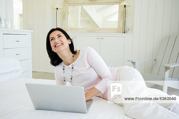 Frau auf dem Bett liegend mit Laptop